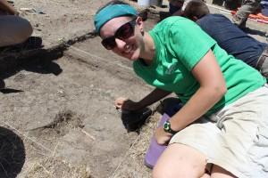 University of Iowa graduate student Amanda Bernemann with the first animal bone discovered in the 2013 season